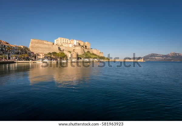 Citadel and harbour entrance at Calvi in the Balagne region of Corsica with clear blue sky and calm waters