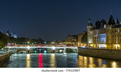 Cite island view with Conciergerie Castle and Pont au Change, over the Seine river timelapse. Night illumination reflecter in water. France, Paris