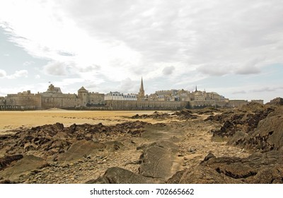 Cited of St Malo at low tide, under a cloudy sky (Brittany, France).