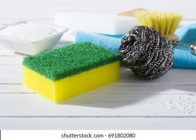 citric acid, cleaning brush, steel wool, sponges and bar of soap on white wooden table background
