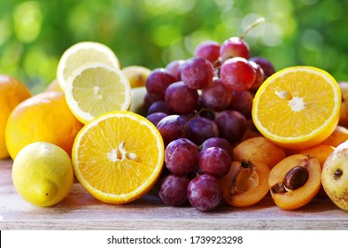 citric fruit , loquat and grapes on table