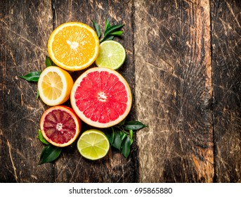 Citrus background. Fresh citrus fruits - Lemons, oranges, limes, grapefruits. On wooden background.