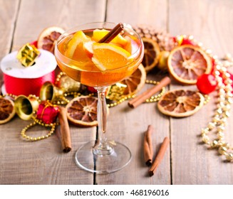 Citrus drink with spices, vintage wooden background.