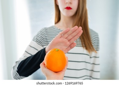 Citrus fruit allergy concept - food intolerance. Young girl refuses to eat orange - shallow depth of field