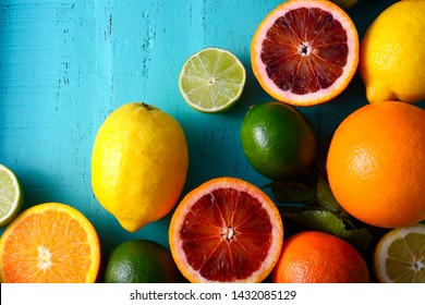 Citrus Fruit on vintage aqua distressed wood table, including navel and blood oranges, lemons and limes.