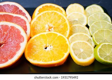 Citrus fruit sliced and arranged on black serving platter