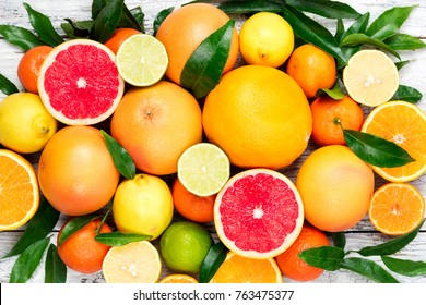 Citrus fruits background. Assorted fresh citrus fruits with leaves. Orange, grapefruit, lemon, lime, tangerine. Top view