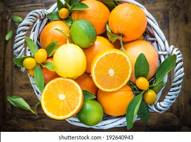 Citrus fruits in basket on rustic wood background.Oranges, limes, grapefruit, lemon,kumquats.
