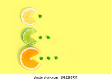 Citrus fruits eating green peas different portion size on creative color paper. Trendy minimal pop art style. Food concept background
