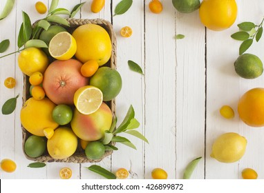 Citrus fruits family in basket on rustic white wooden background. Overhead view. Text space image.