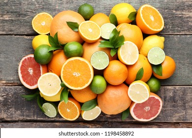 Citrus fruits with green leafs on grey wooden table