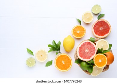 Citrus fruits with green leafs on white wooden table