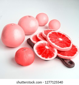 Citrus fruits - lemons, grapefruits, mandarins, oranges - on white tables. Pink