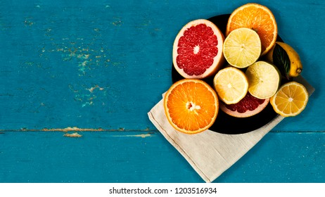 Citrus fruits on old blue wooden table. Top view. Bright colors. Copy space.