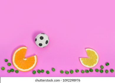 Citrus fruits playing soccer on creative color pink paper background. Trendy minimal pop art style. Concept of football game with colorful food.