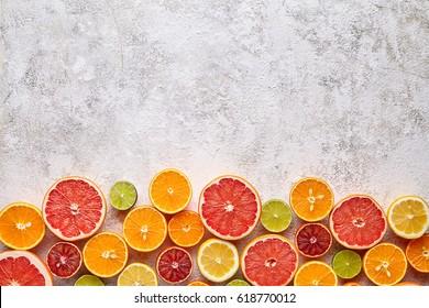 Citrus fruits vegan vitamin mix flat lay on white background, healthy vegetarian organic food, antioxidant detox diet. Tropical summer mix grapefruit, orange, apple, mandarin, sliced kiwi fruit, lime