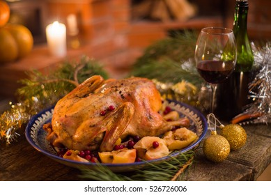 Citrus glazed roasted duck stuffed with rice, garnished with apples, kumquats, and sage. Christmas decorated setting
