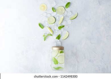 Citrus infused lemonade water with lemon sliced , healthy and detox water drink in summer on concrete table. Health care, fitness, diet concept.