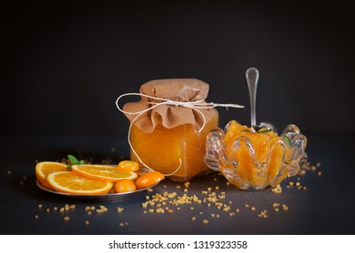 the citrus jam in the glass jar and in the saucer and sliced orange on the dark table
