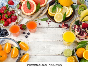 Citrus juice, fresh fruits and berries on white wooden background. Healthy eating, dieting. Top view