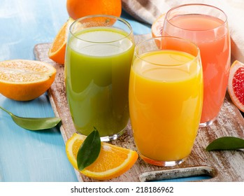 Citrus juice and fruits  on wooden background. Selective focus