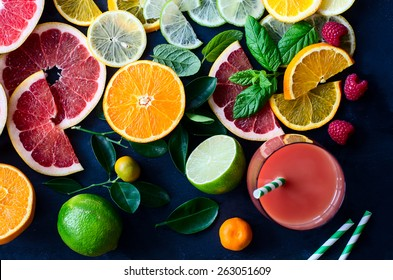 Citrus juice and slices of orange, grapefruit, lemon. Vitamin C. Black background