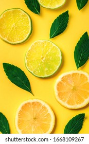 Citrus lemon and lime slices and mint herbs pattern on yellow background. Top view. Minimal design background.