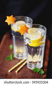 Citrus lemonade with fresh lemon, orange, mint and ice on wooden background