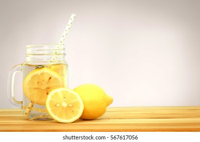 Citrus lemonade water with lemon sliced , healthy and detox water drink in summer on wooden table . vintage color tone