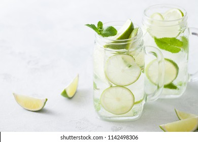 Citrus lemonade water with lime sliced , healthy and detox water drink in summer on concrete table. Health care, fitness, diet concept.