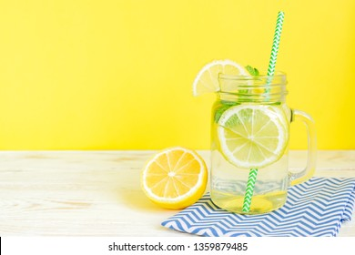 Citrus lemonade water with sliced lemon and mint leaves, healthy and detox water drink in summer on wooden table with bright yellow  background