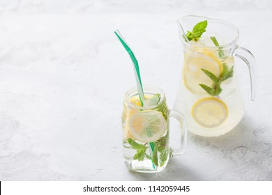Citrus linfused emonade water with lemon sliced , healthy and detox water drink in summer on concrete table. Health care, fitness, diet concept.