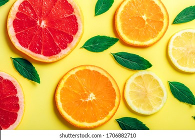 Citrus orange, lemon, and grapefruit slices and mint herbs pattern on yellow background. Top view. Minimal design background.