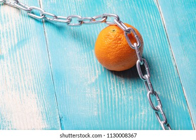 citrus orange on a blue painted wooden table, on an orange metal chain