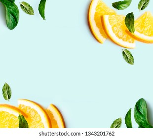 Citrus slices and mint herbs frame on retro mint pastel background with copyspace from above. Top view of lemon and orange refreshment. Summer fruit smoothie minimal banner design. Flat lay.