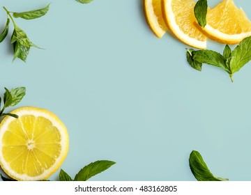 Citrus slices and mint herbs frame on retro mint pastel background with copyspace from above. Top view of lemon and orange refreshment. Summer fruit smoothie minimal banner design.
