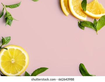Citrus slices and mint herbs frame on retro pastel pink background with copyspace from above. Top view of lemon and orange frame design banner.