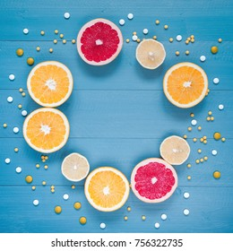 Citrus and tablets frame on the blue wooden background. Vitamin C in the fruits and pills.