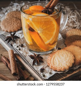 Citrus tea with cinnamon and cardomom in a glass. With sweet homemade almond cookies. Country style. Kraft paper. Wooden background. Close-up.