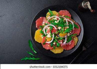 Citrus vitamin salad. Orange, grapefruit, ricotta cheese, pine nuts, red onions and arugula with olive oil in ceramic plate on black concrete background. Selective focus. Top view. Copy space.
