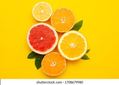 Zitrusfrüchte auf gelbem Hintergrund mit Kopienraum, Obstflatlay, minimaler Sommerverbund mit Grapefruit, Zitrone, Mandarin und Orange
