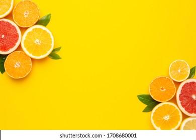 Citruses fruits on yellow background with copyspace, fruit flatlay, summer minimal compositon with grapefruit, lemon, mandarin and orange