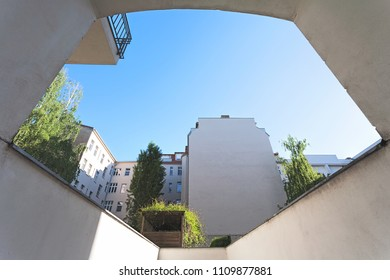 City apartment building yard, on a clear, blue sunny day,  perspective from a garage driveway
