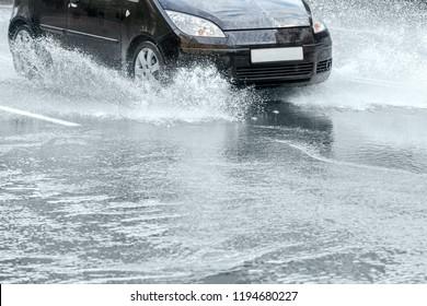 city asphalt road during heavy rain. black car in motion. water splashing from car wheels