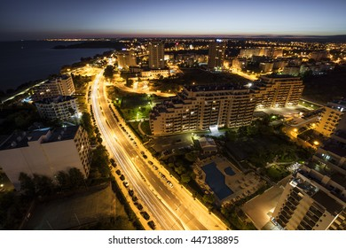 City at the bank of the ocean with buildings and hotels during sunset. View from above. Portimao, Algarve, Portugal.