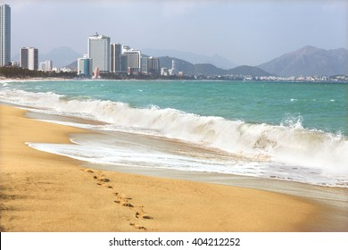 city beach and beautiful waves with a view of the skyscrapers