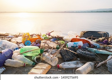 City beach, Varna, Bulgaria. June, 2019. Spilled garbage on the beach of a big city on a sunset day. Empty used dirty plastic bottles, household rubbish. Dirty sea, sandy coast of the Black Sea.