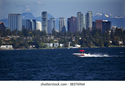 City of Bellevue from Lake Washington with Speed Boat and Snow Capped Mountains in Background
