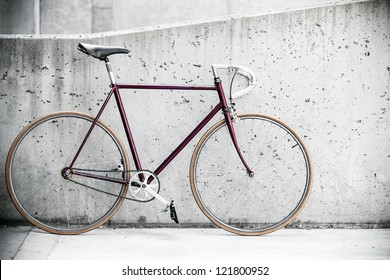 City bicycle fixed gear and concrete wall, vintage old retro bike, cycling or commuting in city urban environment, ecological transportation concept