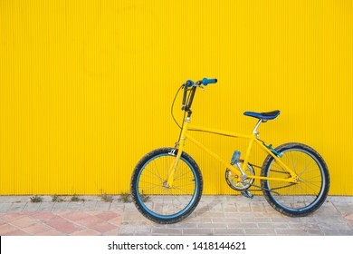 City bicycle fixed gear on yellow wall.